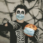 Happy Halloween,kid wearing medical mask in a skeleton costume with halloween pumpkin	over gray background